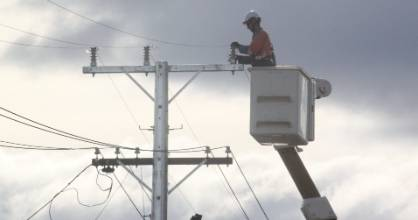A linesman works on a power pole in Cromwell as part of Aurora Energy's Fast Track pole programme.