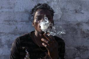 Malawian migrant Jonas smokes marijuana on the rooftop of an abandoned building in downtown Johannesburg, South Africa. ...