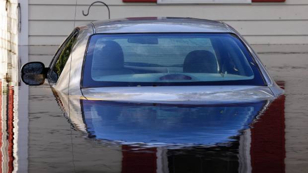 A submerged car sits surrounded by water outside a home in a flooded neighbourhood in Lumberton North Carolina in the