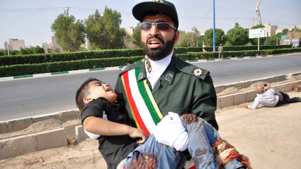 A Revolutionary Guard member carries a wounded boy after the attack by unknown militants