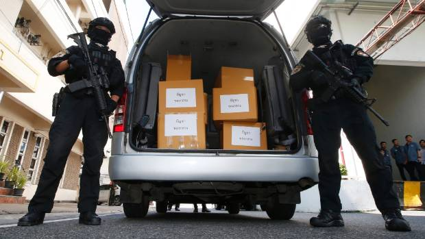 Thai policemen stand guard next to 100kg of seized marijuana before a news conference in Bangkok, Thailand.