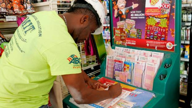 Jean Pierre fills out several Mega Millions lottery tickets for purchase in Orlando Florida
