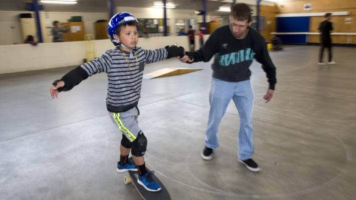 Neko Blythe, 7, has a skate, assisted by James Tuckey, at an event for children with autism.