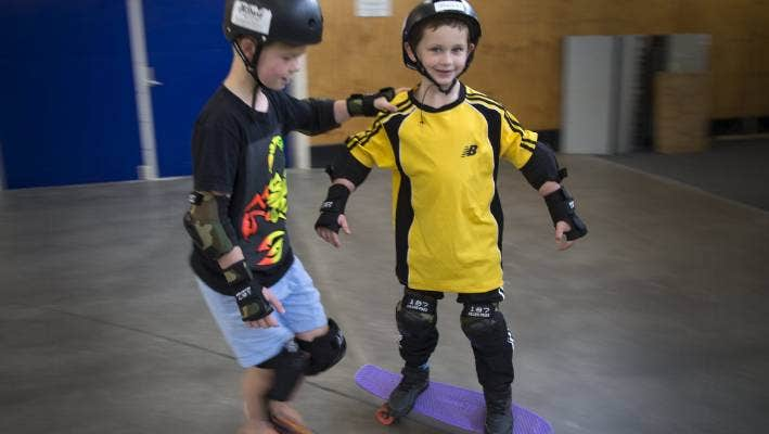 Billy Pratt has a skate at an event for children with autism, assisted by Rian MacDonald.