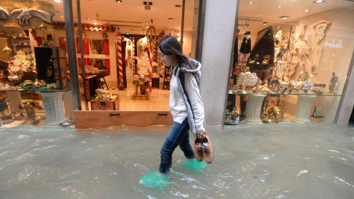 A woman walks in a flooded street of Venice Italy. According to city officials 70 per cent of the lagoon city was flooded by waters rising 1.49m above sea level