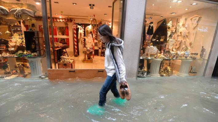 A woman walks in a flooded street of Venice, Italy. If we don't do something to stem the tide, scenes like these will become more common.
