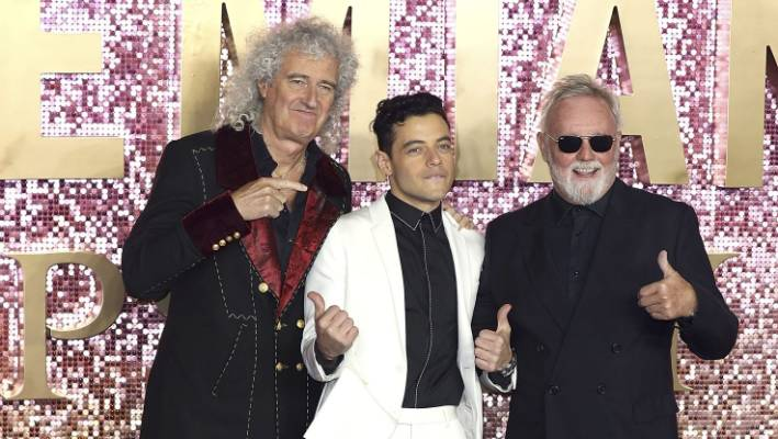 Brian May, left, and Roger Taylor, right, of Queen, and Rami Malek, who plays singer Freddie Mercury celebrate the release of Bohemian Rhapsody.