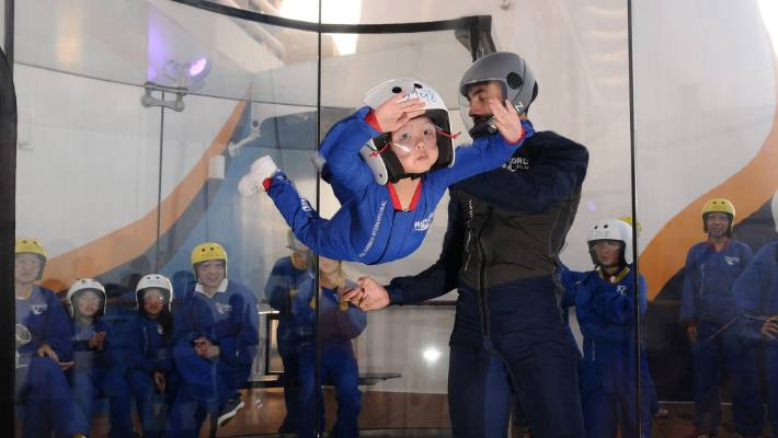 "Byron teaches a young passenger to ""fly"" in the skydiving simulator."