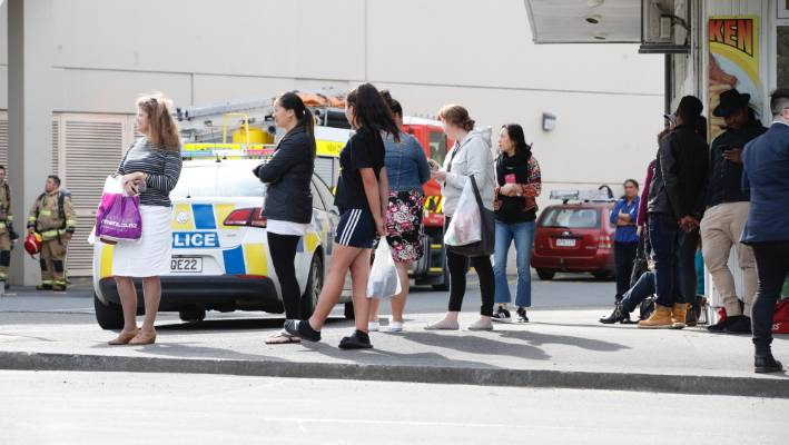 Evacuated shoppers watch on as emergency services arrive.