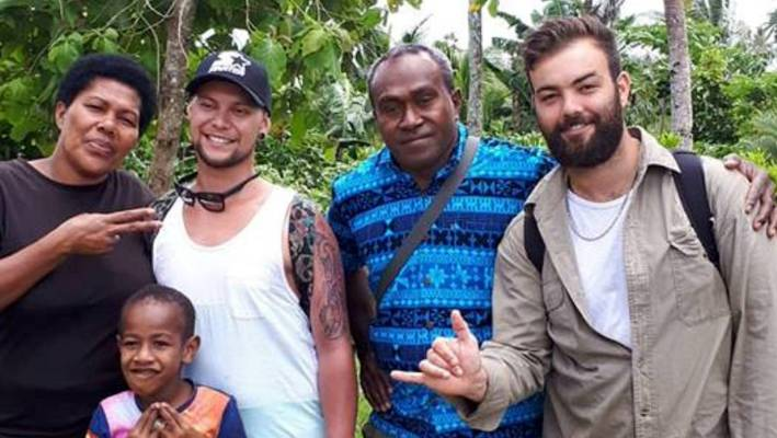 Jarred Thompson (second left) and his friend Thomas Brook (right) in a Fiji village before Thompson fell ill.