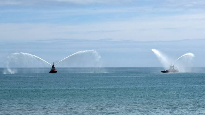Port Taranaki tugs saluted by spraying seawater.