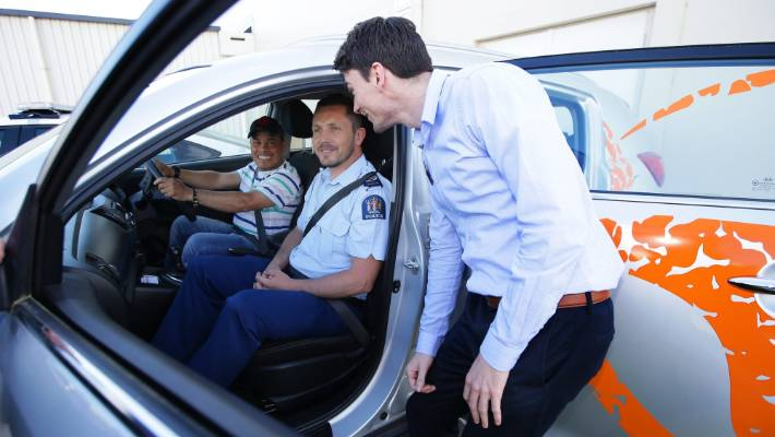 Former Colombian refugee Mauricio Calero takes the wheel on the passenger seat of Jon Bisset, Senior Officer of the Head of Police in the Southland Circuit, and Callum Clark's Project Manager for the Red Cross Refugees Program.