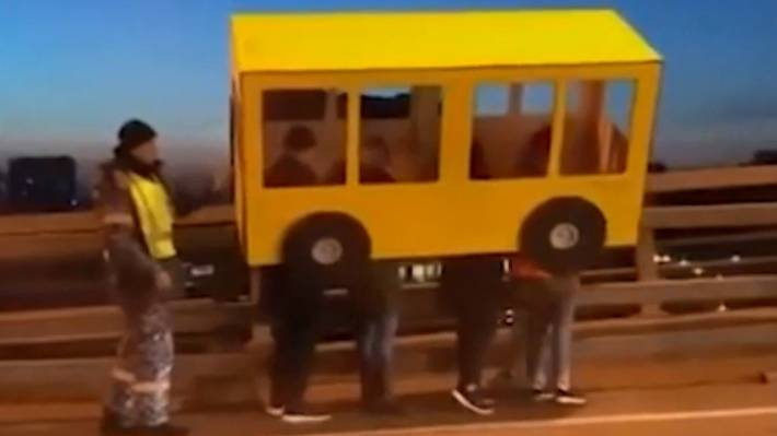 Men Dressed Up As A Bus To Cross Vehicle-Only Bridge