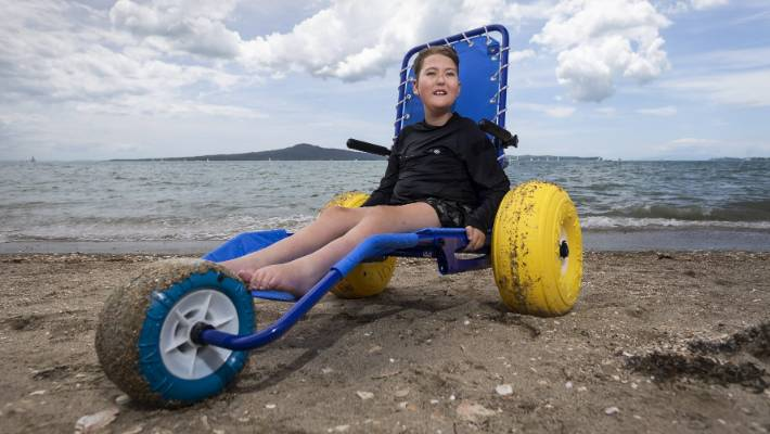 Thomas Morrison tries his new wheelchair on Kohimarama beach in Auckland.