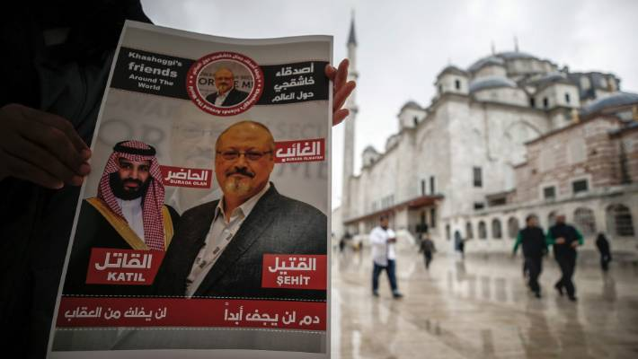 "A man holds a poster showing images of Saudi Crown Prince Muhammed bin Salman and murdered journalist Jamal Khashoggi, describing the prince as ""assassin"" and Khashoggi as ""martyr"" during funeral prayers in absentia for Khashoggi. — Photograph: Associated Press."