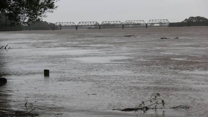 The Clutha River in a flood near Balclut, leading to a railway bridge, where a flood barrier barrier was built to protect the city from possible flooding.