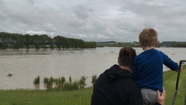 Mother and son are looking at the climbing river Clutha near Balcluth.