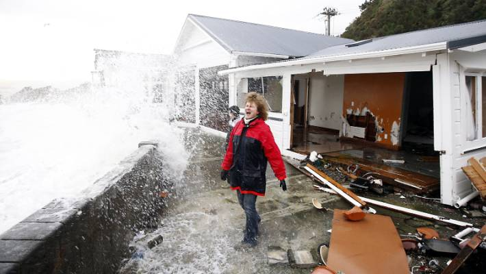 Days Bay resident Sarah Gilbert braces against a storm in 2016. Her  property suffered extensive damage. Sea level change will make it increasingly hard for Lower Hutt residents to get house insurance.