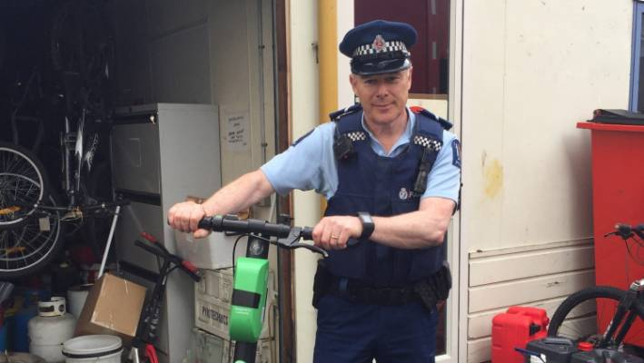 Blenheim Community Officer Russ Smith and one of two lime scooters salvaged from Marlborough.