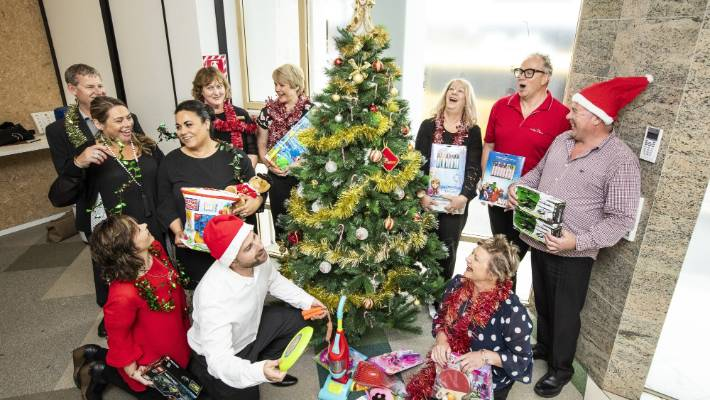 mike pero real estate staff have bought presents to put under the nelson mail christmas tree