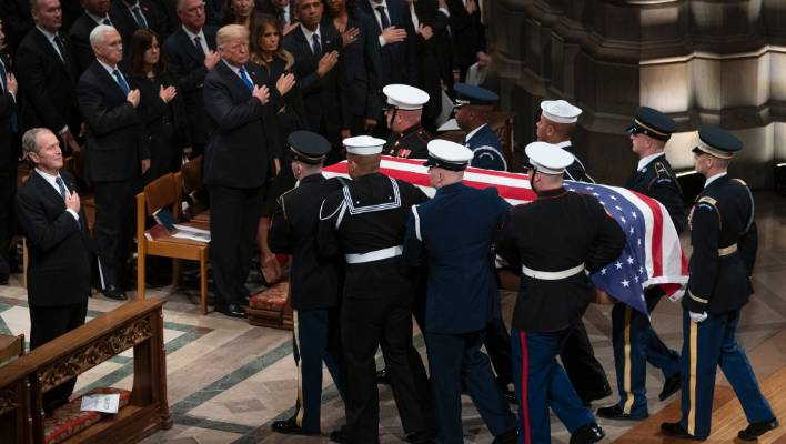 The US flag-draped casket of former President George HW Bush is carried by a military honour guard.