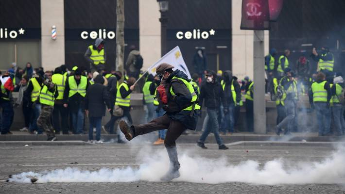 Teargas surrounds protesters as they take part in the 'yellow vests' demonstration near the Arc de Triomphe.