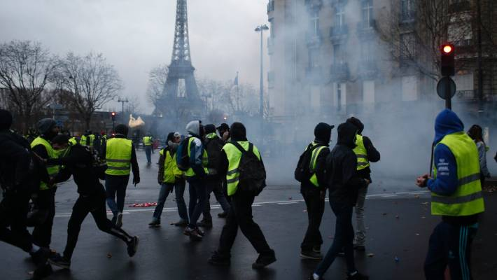 Demonstrators walk through tear gas during clashes on Saturday.