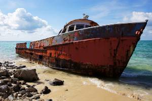 A corroding fishing boat, abandoned after its captain passed away, lists on a beach in Exuma Sound on Cat Island, Bahamas.
