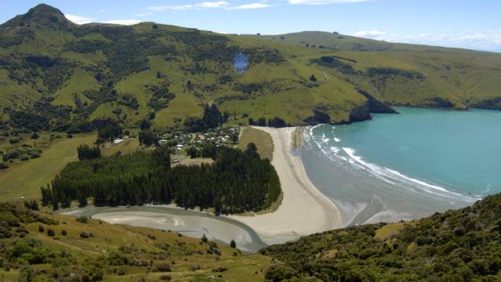 Le Bons Bay is a quintessential Kiwi bach bay. A cluster of houses sits behind low dunes, in front of a wide beach with slow-crashing waves.