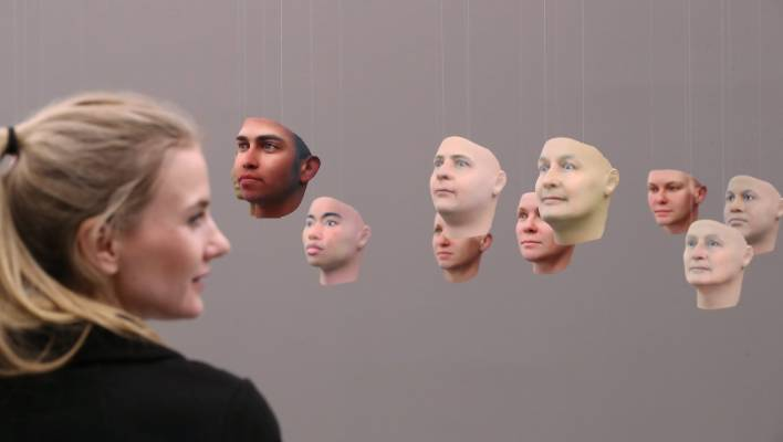 """A visitor looks at 3D-printed faces of what could be Chelsea Manning, according to Manning's DNA in the installation """"A Becoming Resemblance"""" by American artist Heather Dewey-Hagborg. The thirty masks are derived from Chelsea Manning's DNA, smuggled out of prison when Manning, then Bradley, was serving time for passing classified information to WikiLeaks."""