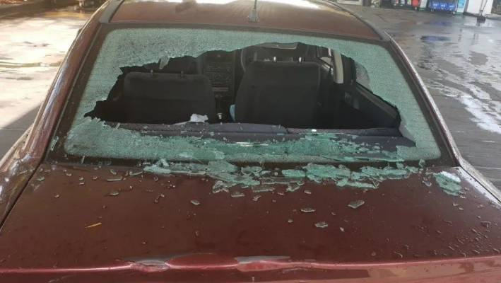 A smashed rear windscreen at a service station in Moorebank, Sydney.