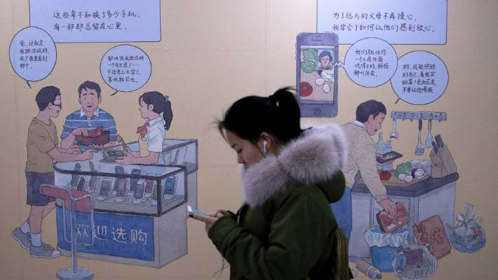 A woman browses her iPhone as she walks by a mural depicting an iPhone and Chinese people buy smartphone to communicate with family members, at a subway station in Beijing.