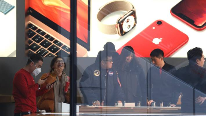Customers visit an Apple store in Beijing, China. The tech giant became the latest global company to collide with Chinese consumer anxiety when CEO Tim Cook said iPhone demand is waning, due mostly to China.