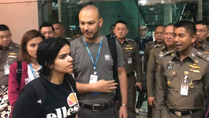 Rahaf Mohammed Alqunun walks by Thailand Chief of Immigration Police Major General Surachate Hakparn, right, before leaving Suvarnabhumi Airport in Bangkok Monday, 7 January.