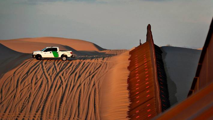 A US Customs and Border Patrol agent patrols a section of floating fence at sunset that runs through Imperial Sand Dunes along the international border with Mexico in Imperial County California