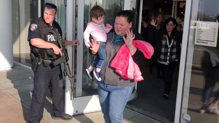 Shoppers with their hands raised are evacuated from a Utah mall after a gunman opened fire