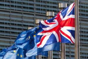 European Union flags and the UK flag flap in the wind.