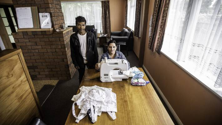 Shenenas Norbasha and her husband Mohammed Norbasha with the sewing machine that Red Cross volunteer Esmee Rowden found for the family.
