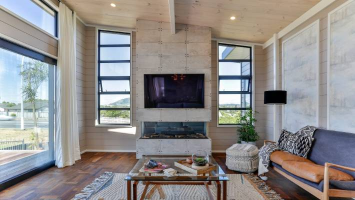 Some wooden walls are painted, and the ceilings are blond. The fireplace surrounds concrete shaped like raw materials.
