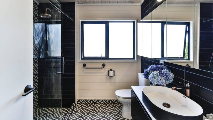 Black tiles are in the bathroom with several rows of walls.