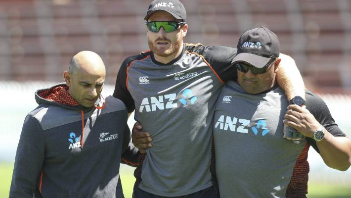 Martin Guptill is assisted off the Basin Reserve after injuring his back at training, by physiotherapist Vijay Vallabh, left, and security manager Terry Minish.