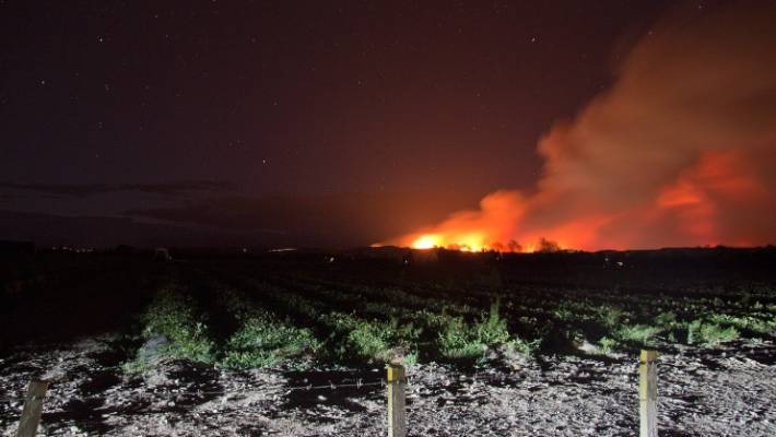 The fire casts an orange glow as it burns across Pigeon Valley in Nelson.