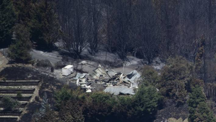 Blackened trees and a flattened home can be seen from the air.