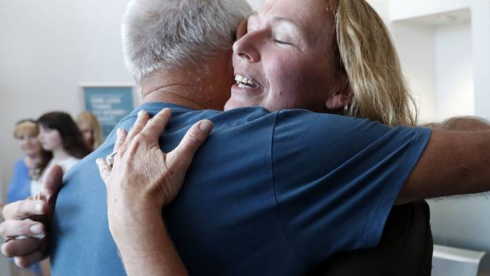 Renton celebrates with a supporter in the Nelson District Court.