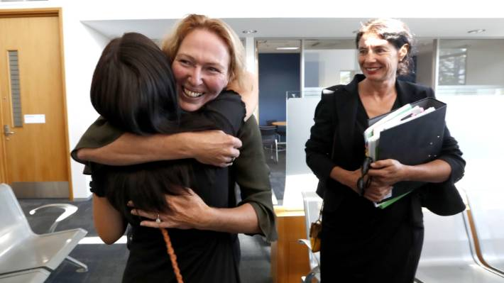 Rose Renton, centre, hugs supporter Scarlett Carver, while her lawyer Sue Grey looks on after Renton was discharged without conviction on a charge of cultivating cannabis.