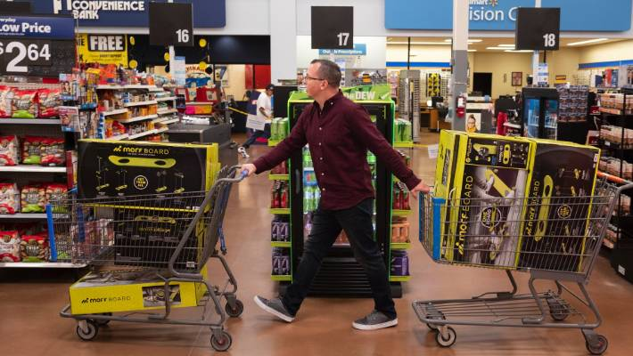 Juston Herbert pushes two carts of Morf Boards, a popular kids toy, through a Walmart in Phoenix.