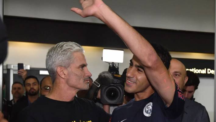 A jubilant Hakeem al-Araibi walks out of Melbourne Airport alongside former Socceroos captain Craig Foster.