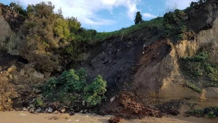 The site of one of two closed landfills located on an eroding cliff face above a beach near Oamaru.