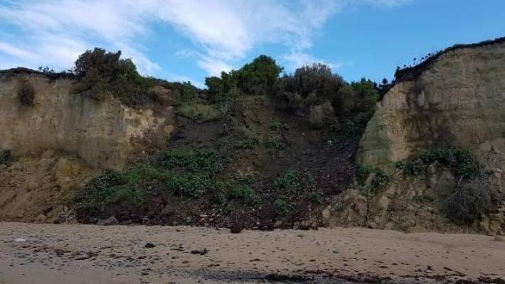 Coastal erosion has resulted in contents of the landfill spilling down the face of the cliff and onto the beach below.