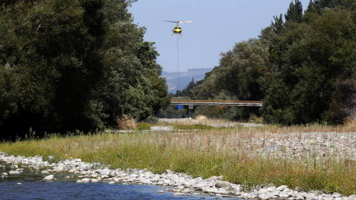 A Central South Island Helicopter fills its monsoon bucket in the Wai-iti River near Wakefield as the battle continues to fight the wildfire that started in Pigeon Valley.